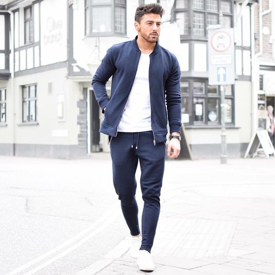 Go for a navy blue bomber jacket and navy blue sweatpants to get a laid-back yet stylish look. A cool pair of white sneakers is an easy way to upgrade your look.   Shop this look on Lookastic: https://lookastic.com/men/looks/navy-bomber-jacket-white-crew-neck-t-shirt-navy-sweatpants/20262   — White Crew-neck T-shirt  — Navy Bomber Jacket  — Navy Sweatpants  — White Plimsolls