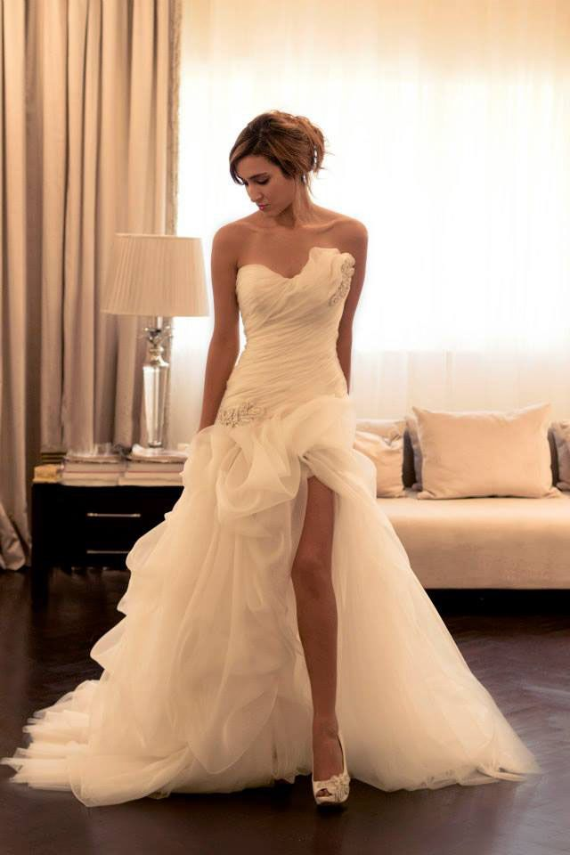 Asymmetrical ruffled slit skirt, ivory strapless custom wedding dress. Pleated sweetheart neckline features one side adorned with beaded ruffles, bias pleated dropped waist accented with one side beaded embellishment. Ball gown skirt offers luxury cascading ruffles and open slit adding drama, v back.  <br>