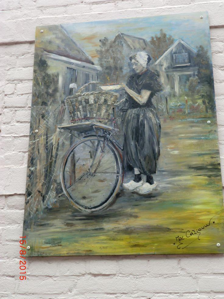 Schilderij met visvrouw bij fiets tegen de gevel