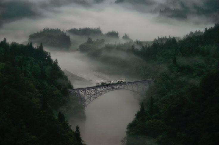 Taken at Mishima town in Fukushima prefecture, Japan. The first train goes across the railway bridge through in morning mist. The train moves forward little by little slowly.