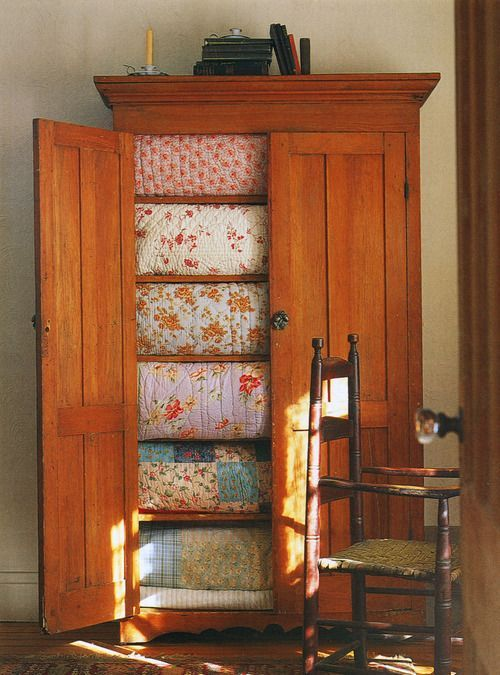 Great Cupboard holding several neatly folded quilts