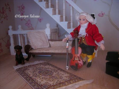 Miniature Mozart and violin ffom Salzburg. On the chaise-longue miniature knit cable pillow.