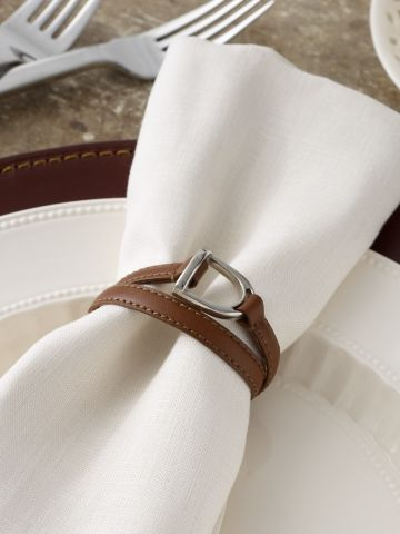 "Dorset Stirrup Napkin Ring - Ralph Lauren Home Serving Pieces - RalphLauren.com $32 Finished with an equestrian-inspired stirrup detail, the Dorset napkin ring is crafted from saddle leather and is the perfect heritage complement to the well-appointed table. Double 3/8"" leather strands with stitched edges attach at the bottom. Item is sold individually, not as a set. Leather. Wipe clean. Imported."