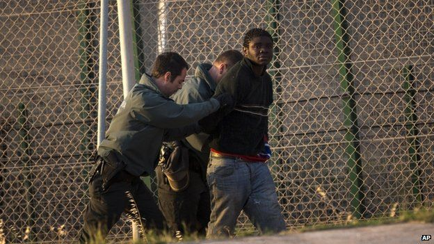 A sub-Saharan migrant is detained and sent back to the Moroccan side by Spanish Guardia Civil officers after scaling a metallic fence that d...