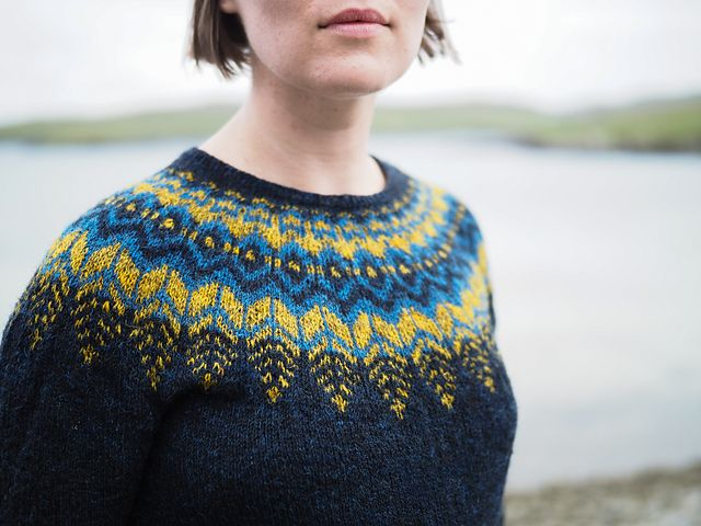 A top-down pullover with a dramatic round yoke. This yoke is inspired by Icelandic Lopapeysas but the finer gauge provides a larger canvas for more intricate patterning. The fairly deep yoke and slightly dropped underarm combine with positive ease for a slouchy, comfortable fit. The colourwork slowly feathers into the main colour avoiding the heaviness and unflattering line across the chest that can sometimes result from deeper yoke patterns. This results in wide gaps between the contrast…
