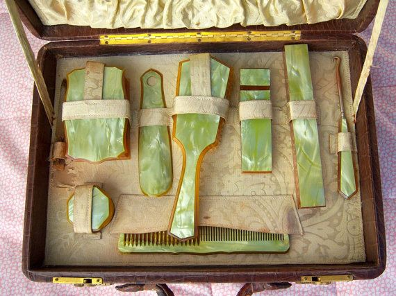 Circa 1910-1920 celery green celluloid boudoir set in original brocade-lined alligator traveling vanity case. Eight pieces: soap box, powder box, shoe horn, hair brush w/blond horse hair, hairpin box, toothbrush box, shoe hook, and comb. The case also has a compartment for lingerie and night clothes.
