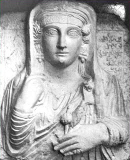 Big-eyed Bilat was buried between 140-170 CE.  She holds her veil with her right hand, raising it to collarbone level, and holds in the other a spindle and distaff. She wears a headband with floral design and a knotted and twisted turban below a veil.  Her jewels are an animal-headed brooch, earrings shaped like a bunch of grapes, and a ring on the little finger of her left hand.