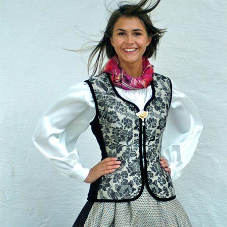 SILKEFIN Silkefin er en helt ny festdrakt i ull, silkedamask og fløyel, med forkle i silke. Damaskstoffene er vevd hos Krivi på Tingvoll, og drakten er designet av Randi Bakken. Silkefin sys av Husfliden Trondheim