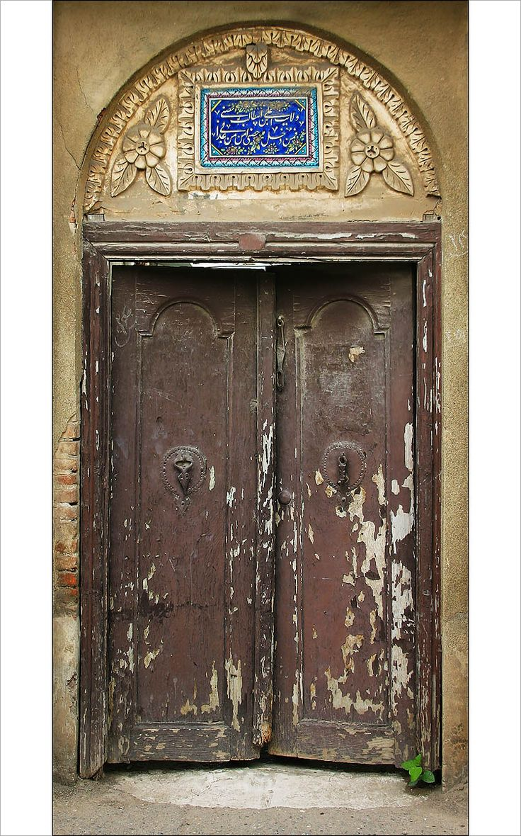 An old wooden door in Rasht, a city close to the Caspian Sea in northern Iran. The two door knockers look different by design; one is for women and the other for men so people inside can tell if the visitor is male or female.