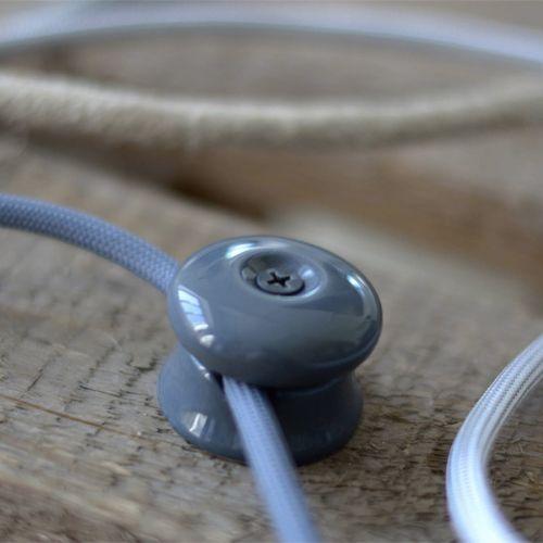 Grip Porcelaine Isolant Gris 1 câble - Grip porcelaine de couleur gris souris, idéal pour les montages muraux et vous permettre de guider et fixer vos câbles au plafond. Ce grip isolant pourra vous permettre le montage de tous vos câbles textiles.