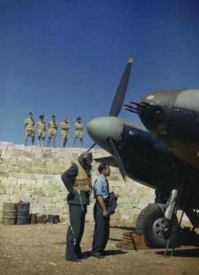 "Malta, Luqa Airfield, June 1943: the Commander of No 23 Squadron, Royal Air Force, Wing Commander John B Selby, DSO, DFC, already on flight dress, and his observer looking at their de Havilland Mosquito II aircraft ""P-Peter"" while other members of the Squadron watch from atop the blast wall at the Dispersal Point. The four 20mm cannon are corked to prevent dirt damaging them. Victor Sierra"