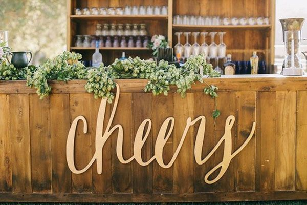 Natural Wood Bar with Gold Laser Cut Signage and a Hops Garland | Brandon Kidd Photography | http://heyweddinglady.com/craft-beer-brewery-wedding-ideas-style/