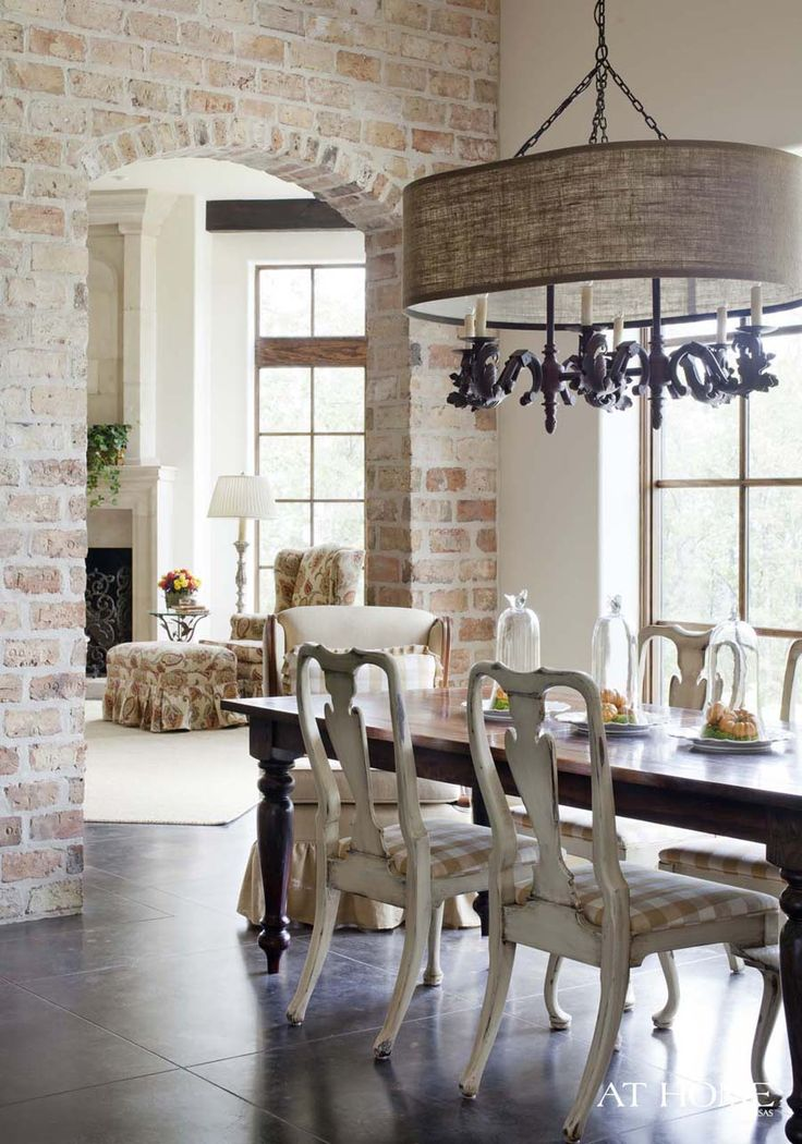 In the breakfast room, the chandelier is from Providence Ltd. Interior Design and an I.O. Metro table blends with heirloom chairs. lovin the brick wall and heirloon chairs