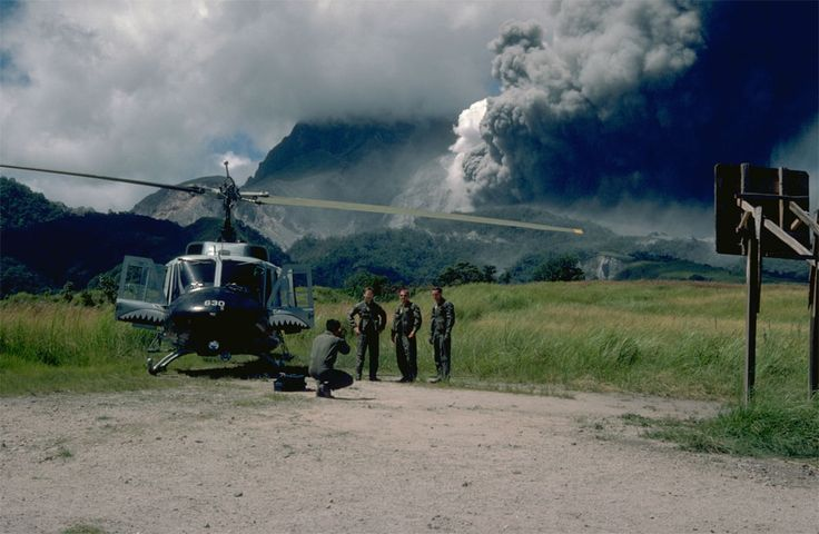 Air Force Officers (at Clark Air Base) are shown in the foreground as Mt. Pinatubo (in the Philippines) erupts in the background on June 12, 1991. Field assessments of the volcano's activity were undertaken just before the colossal eruption.