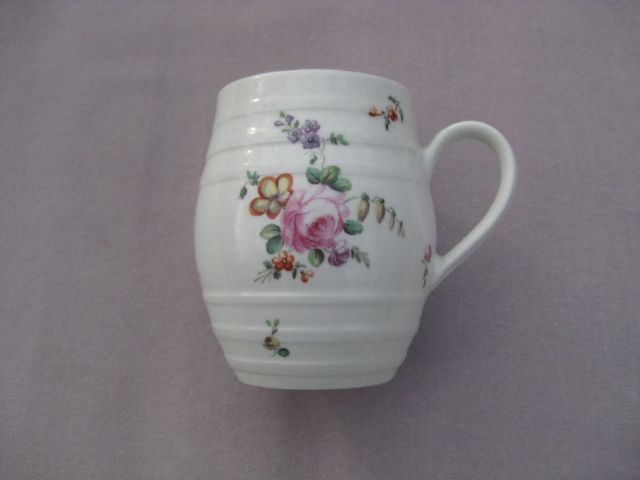 """A Derby mug of barrel  shape and vertical ribs and a moulded handle. Nicely painted with sprays of English flowers and a brown lined rim. Unmarked   Circa  1765 Height 4 1/2"""""""