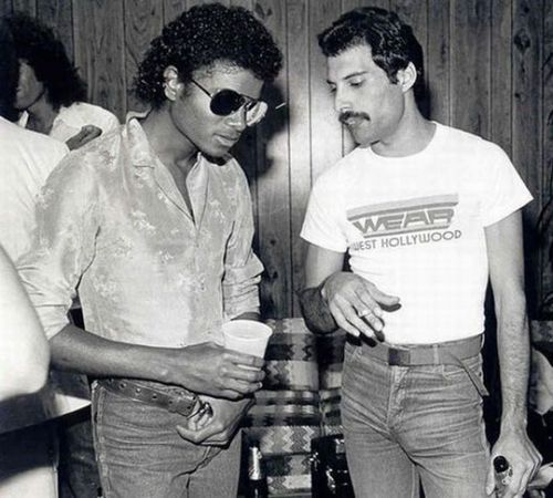 Freddie Mercury and Michael Jackson | I wonder what they are talking about | brilliant artists in their own right | famous musicians and performers | ray bans | soda and beer | party | 1970's fashion | velour shirt | black white | discussion | chat | iconic | history | fro | afro | RIP | moustache | listen | talk | converse