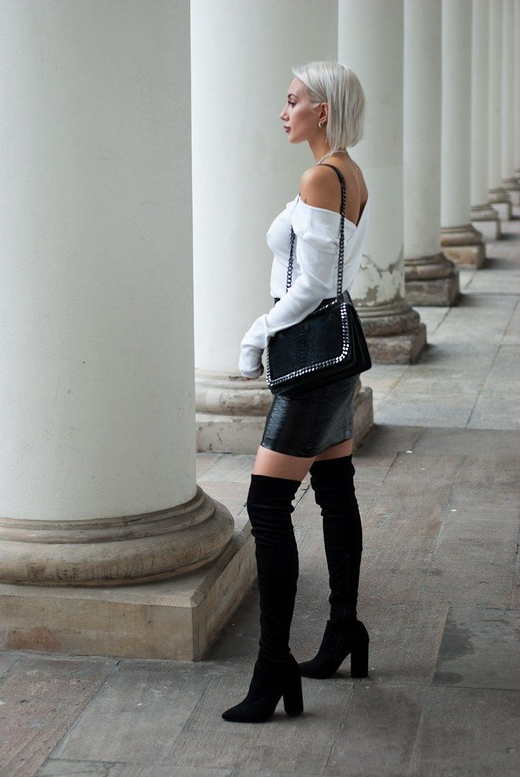 Monika Sikocińska wearing black over the knee boots paired with a black leather skirt and white open back sweater. A great look!