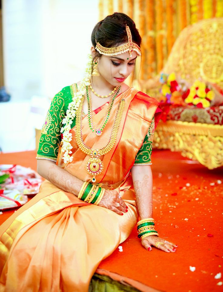 South Indian bride. Gold Indian bridal jewelry.Temple jewelry. Jhumkis. Orange silk kanchipuram sari with contrast green blouse.Braid with fresh jasmine flowers. Tamil bride. Telugu bride. Kannada bride. Hindu bride. Malayalee bride.Kerala bride.South Indian wedding.