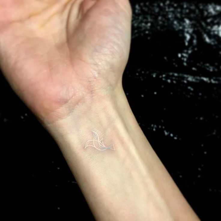 White ink dove tattoo on the wrist.