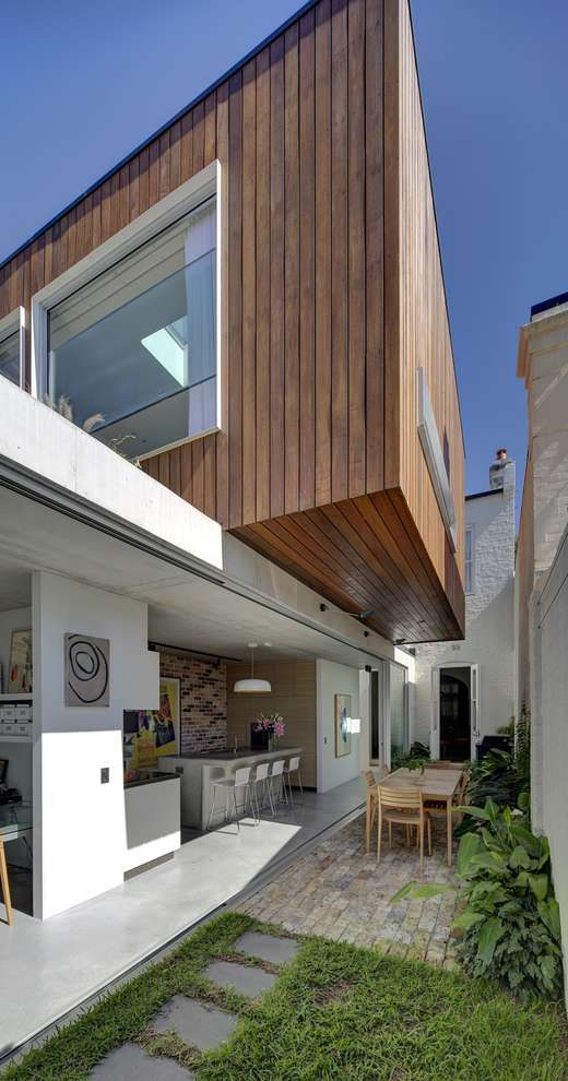 """A modern extension to an inner Sydney house sees contemporary concrete and timber """"boxes"""" provide the owners with courtyard living as well as extra living space. Love the sliding walls that open the inside to the out as well as the second garden on the roof. Long Courtyard House by Scale Architecture."""
