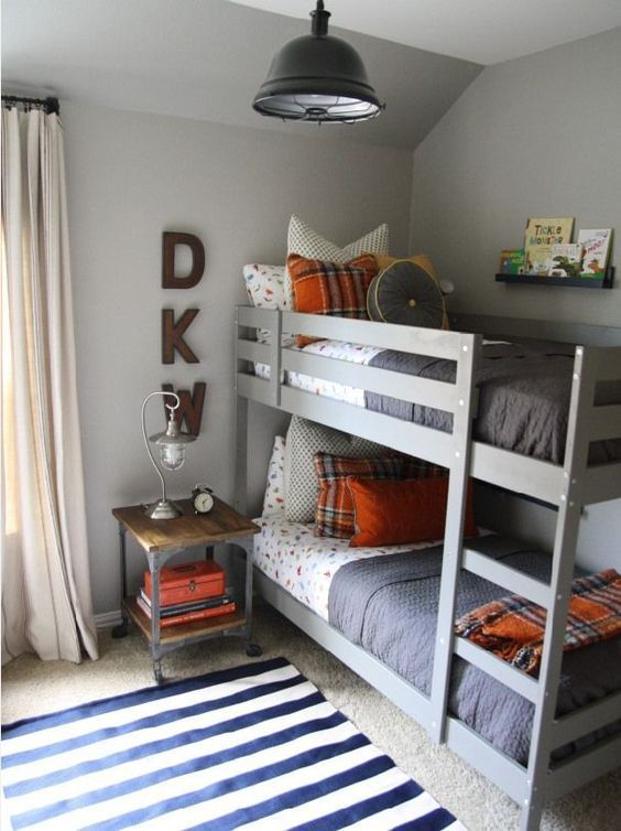 gray and orange bedroom. a cute gray and orange boys bedroom with bunk bed, small nightstand schoolhouse-inspired metal light. by holly mathis interiors