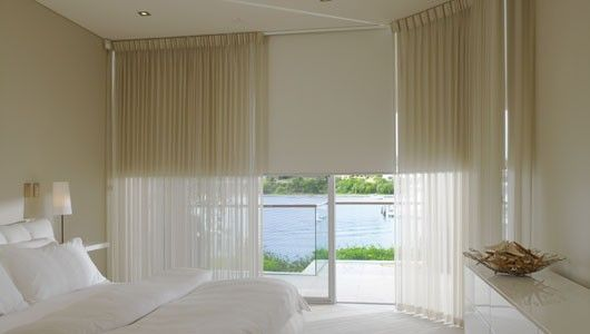 I like the practicality of roller blinds with a sheer curtain for softness: