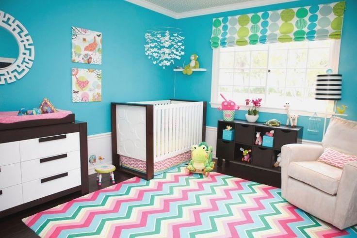 chambre bébé colorée avec un tapis à motif chevron multicolore, rideau blanc à pois multicolores et peinture murale turquoise