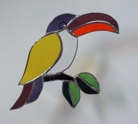 Echt kleurrijke gebrandschilderd glas Toucan, met een schuine rand voor zijn buik. Deze foto vangen niet de schittering van de schuine kant. Wanneer de zon het precies goed raakt, gooit het regenbogen van kleur in de kamer. Zijn hoofd is een diep paarse terwijl zijn snavel een lichter paars en oranje is. Zijn staart zijn de twee tinten van paars en zijn vleugels is helder geel. Branch is bruin en de bladeren zijn twee tinten groen. Hij is echt een eyecatcher! Hij meet 9 door 5.5. Ik gift…