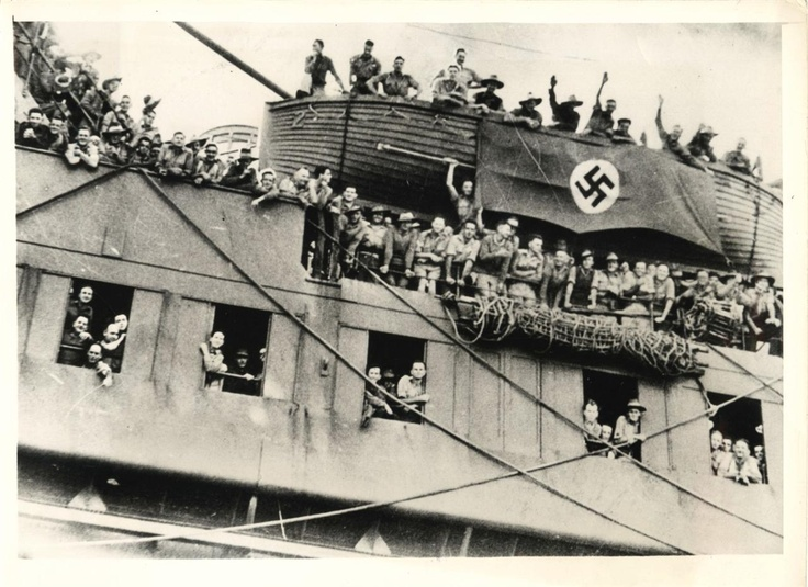 1943- Troops of the 9th Australian Division display captured German flag as they arrive at home port.