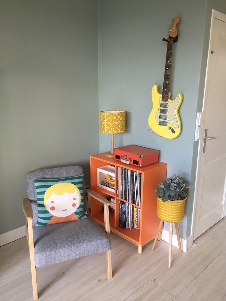 Muziekhoek woonkamer. Lamp Orla Kiely. Gele plantenmand op poten van Handed By. Kussen Donna Wilson. Stoel Ekenaset Ikea, licht geschuurd.