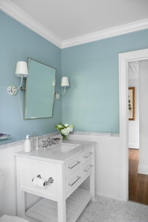 Simple and  pretty restroom. Love the vanity, white tile wainscot, tilted mirror and sconces. The clear soap dispenser is amazing too.