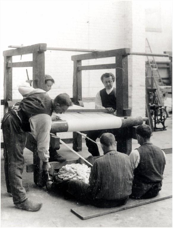 Wevers in de textielfabriek van Dissel [Tongelresestraat nr. 56]. Met linksboven Jan van Postel, linksonder Sanders (vader van Chef Sanders), rechtsboven Ant. Louwers; rechtsonder Jan van den Berk, middenonder Geert Sanders bijgenaamd de Bakker. Deze mannen zijn een boom aan het opzetten Auteur: Tollens, Henricus Jacobus - 1905