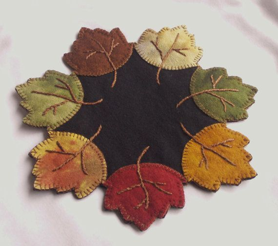 "Add some primitive fall décor to your home with this beautiful wool penny rug, candle or table mat. Made from a variety of beautiful hand dyed wools, this piece is about 10½"" in diameter and is completely hand stitched with a medium brown heavy thread that displays the veining detail of each leaf. Each leaf is different in color tone, mottling, and texture to give this piece a one of a kind look, just like every leaf is in nature. The perimeter has been blanket stitched securing each leaf to…"