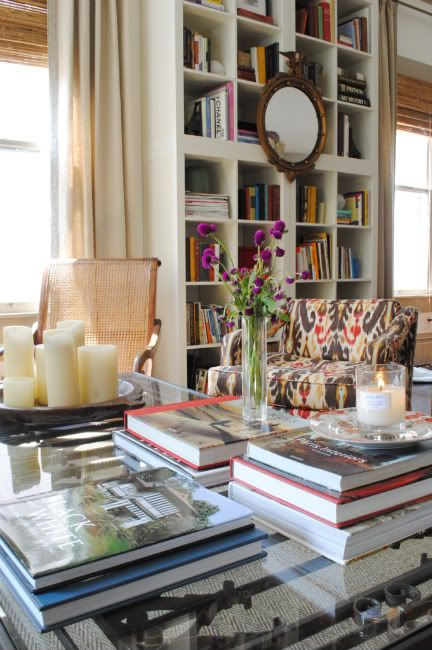 Add height to a room with bookcases! I love the ikat print chair, the chunky candles, and the stack of books on the table!
