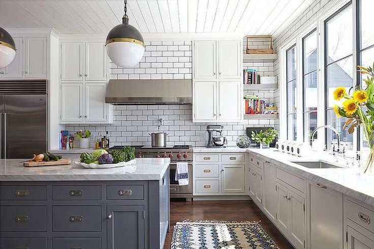 Beautiful kitchen features white plank ceiling lined with Hicks Pendants illuminating gray island accented with campaign hardware topped with white marble.