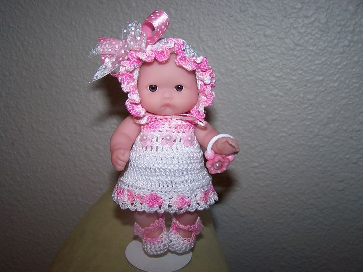 # 950 Sweet pink/white crochet dress with matching bonnet and holding a rattle.