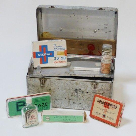 Boîte métallique à pharmacie, teinture d'arnica, alcool de menthe, alcool à 90°, flacon de mélisse des Carmes vide, coton hydrophile ROCA, tube de 30g de Phénergan, tube de 30g d'Hémoclar, bande extensible Tricosteril, boîte de Solucamphre, boîte de 10 compresses Larochette, pansements Biogaze ... (ATTENTION, cette objet est vendu à usage décoratif uniquement, nous vous conseillons de ne rien utiliser pour tout autre usage)