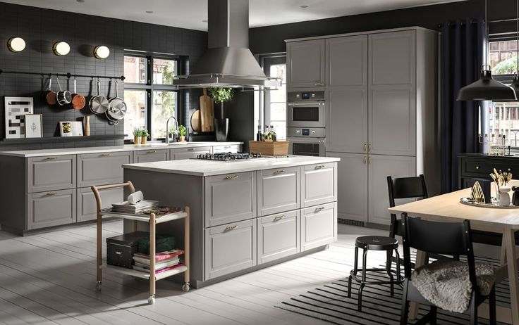 A large grey and black kitchen with an island in the centre.