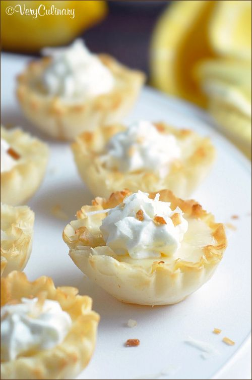 Small fillo (or phyllo) shells are filled with a lemon custard and topped with whipped cream and toasted coconut!