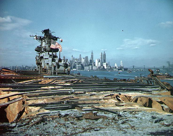Damaged carrier USS Franklin in New York Harbor, New York, circa 28 Apr 1945; note Manhattan skyline in background. (US National Archives)