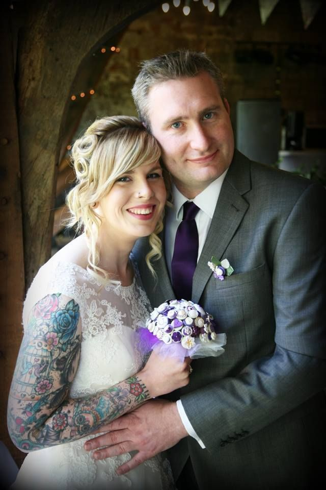 A stunning purple vintage bouquet which matches the brides tattoos and just looks amazing in this wedding photo!