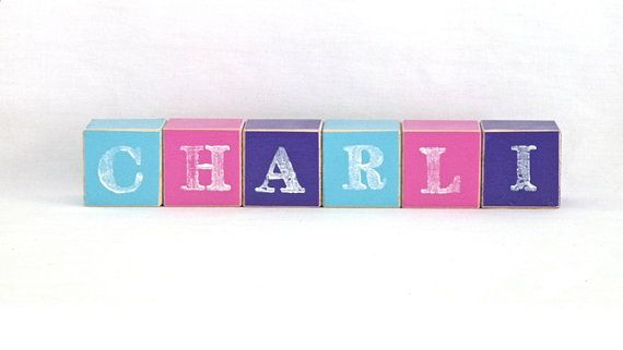 Personalised Wooden Blocks make the perfect addition to any nursery. Place the baby blocks on a bookshelf, dresser or use them as a wooden toy. Wooden baby blocks also make a wonderful new baby gift that can double as a photo prop. Wooden name sign blocks can be custom coloured to match you nursery decor.  Small blocks are 4.2 cm square (made of pine), hand painted with water based paint and stamped with your childs name. To add to their unique look, wooden blocks have been sanded to give…