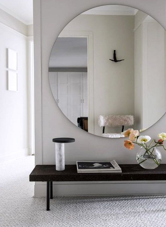 large circular mirror above black bench in modern entry way / sfgirlbybay