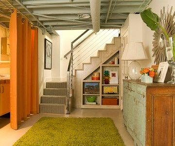 grey unfinished basement ceiling   storage under stair   stair hand rail   light colored flooring