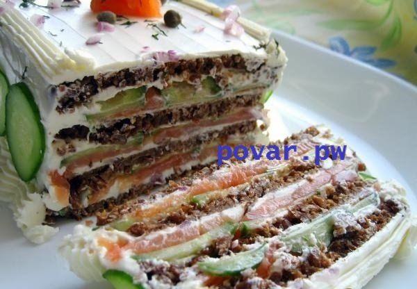 Бутербродный торт с копченым лососем и мягким сыром  Ингредиенты: -Хлеб цельнозерновой 4 ломт. -Сыр мягкий сливочный 340 г -Лук красный 1 ст.л -Укроп 3 ст.л -Каперсы консервированные 1 ст.л -Лимонный сок 1 ст.л -Соль щепотка -Перец свежемолотый по вкусу -Лосось копченый 200 г -Огурец 2 шт.  Приготовление: 1. Разделить крем-сыр на две части. Выложите половину сыра в миску, сбрызните лимонным соком, добавьте мелко порубленный лук и укроп, щепотку соли, каперсы и свежемолотый перец. 2…
