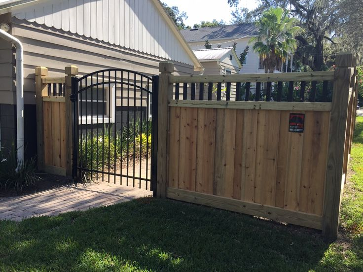 Custom wood privacy fence and scalloped aluminum gate designed and installed by Mossy Oak Fence Company in Orlando and Melbourne, Florida