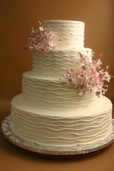 white buttercream frosting with white waved lines on all layers. Bouquet of shades of pink and shite stephanotis