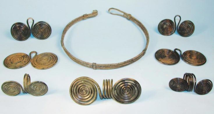 Late Bronze Age European Spiral Torque and Ornaments group of jewelry including a torque made up of a three-fold spiral bronze wire, three double spectacle hair rings, and four double spiral pendants