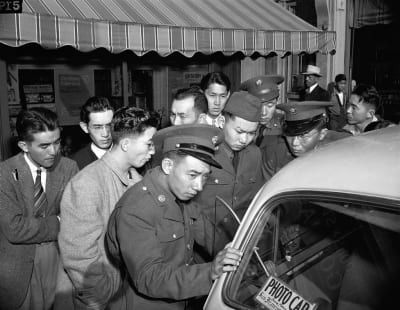 The next day, young Japanese-Americans, including several Army selectees, gather around a reporter's car in the Japanese section of San Francisco. Over 30,000 second generation Japanese Americans volunteered or were drafted into the U.S Army during World War II.