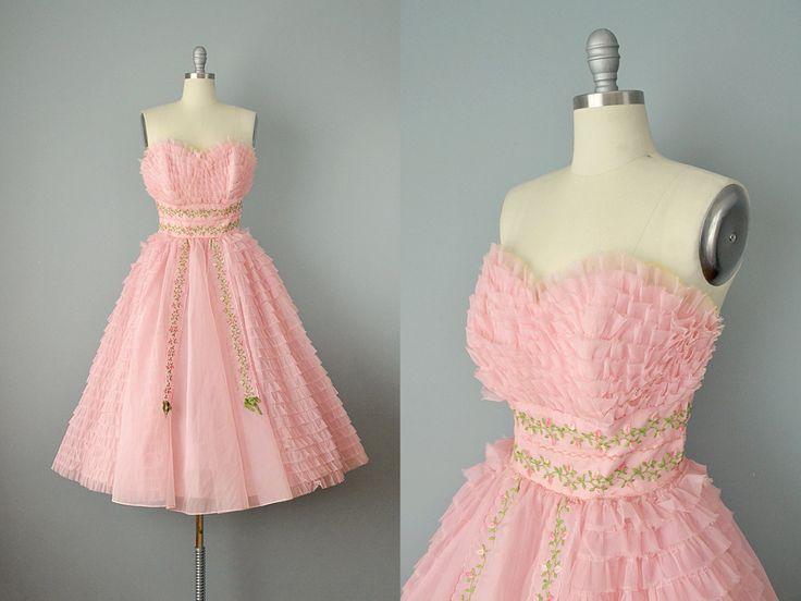 Een heerlijke confectie van een jurk van de 1950, gemaakt van lagen van roze chiffon, tulle en taffeta. De top beschikt over een uitgebeend bodice, sweetheart hals, is gemaakt van lagen van gegolfde chiffon met een ruwe rand aangesloten op tulle en is bekleed in roze taffeta. De rok echos van de lagen van ruwe randen chiffon over tulle, en beschikt over een voorpaneel van borduurwerk in een delicate rosebud-motief. Het borduurwerk optreedt weer in de achterkant van de rok, en langs de brede…